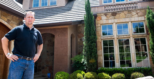 Keith G stands in front of his UFCU financed home
