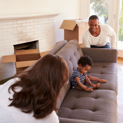 Couple moves a sofa into their new house.