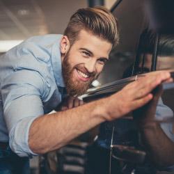 Happy man inspecting car at car dealership