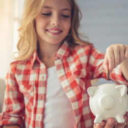 Father helping young daughter put coins in piggy bank