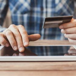 Man using a credit card to make a purchase online.